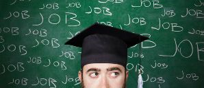 new grad in front of chalkboard