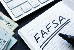 a desktop with a notebook that says fafsa