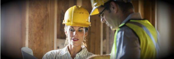 A female construction manager shares a blueprint with a worker.